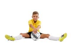 一个逗人喜爱的男孩以黄色在他的手上炫耀制服举行一个球,在白色背景隔绝的年轻足球运动员 免版税库存图片