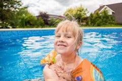 一个逗人喜爱的白肤金发的女婴游泳在与蓝色色的水户外,微笑和举行父母` s手的swimmig水池 库存照片