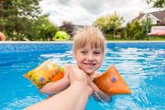 一个逗人喜爱的白肤金发的女婴游泳在与蓝色色的水户外,微笑和举行父母` s手的swimmig水池 图库摄影