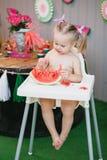 一个逗人喜爱的白肤金发的女孩在儿童` s白色椅子坐并且吃切片一个水多的西瓜在夏天 免版税库存照片