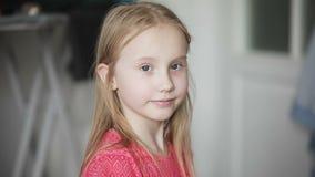 一个逗人喜爱的白肤金发的女孩的画象 孩子看照相机 股票视频