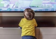一个逗人喜爱的白肤金发的男孩在客厅看电视非常接近它, 免版税图库摄影