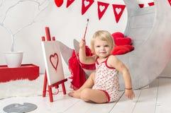 一个逗人喜爱的矮小的女婴的画象在华伦泰` s天的一个装饰的假日演播室 免版税库存照片