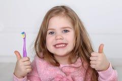 一个逗人喜爱的矮小的白肤金发的女孩刷牙 免版税库存图片