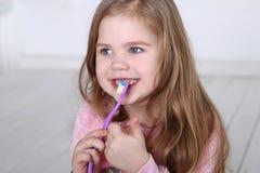 一个逗人喜爱的矮小的白肤金发的女孩刷牙 免版税图库摄影