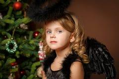 一个逗人喜爱的矮小的白肤金发的女孩的特写镜头画象有蓝眼睛的在以圣诞节为背景的一套黑邪魔邪魔服装 库存照片