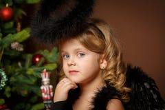 一个逗人喜爱的矮小的白肤金发的女孩的特写镜头画象有蓝眼睛的在以圣诞节为背景的一套黑邪魔邪魔服装 免版税库存照片