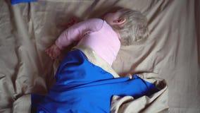 一个逗人喜爱的矮小的被唤醒的小孩在一条蓝色毯子在它的边和冻结转动,然后转动 一点女婴 股票录像