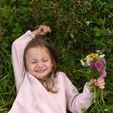 一个逗人喜爱的笑的小女孩,放置在草和采取领域流程花束  免版税库存照片