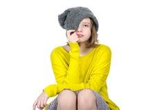 一个逗人喜爱的青少年的女孩的画象,拉扯他的在她的面孔的盖帽 免版税库存图片