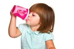 一个逗人喜爱的饮用的小小孩女孩的画象 库存图片