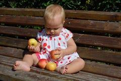 一个逗人喜爱的11个月婴孩用四个苹果 免版税库存图片