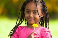 一个逗人喜爱的年轻黑人女孩的室外画象-非洲人民 免版税库存图片