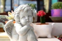 一个逗人喜爱的婴儿天使的雕象 免版税库存图片