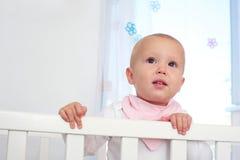 一个逗人喜爱的婴孩的水平的画象小儿床的 库存照片