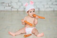 一个逗人喜爱的婴孩的画象在坐复活节兔子的耳朵穿戴了和 免版税库存照片
