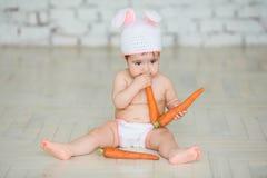 一个逗人喜爱的婴孩的画象在复活节兔子耳朵穿戴了 免版税库存照片