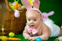 一个逗人喜爱的滑稽的婴孩的画象在复活节兔子耳朵穿戴了用鸡蛋 免版税图库摄影
