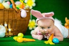 一个逗人喜爱的滑稽的婴孩的画象在复活节兔子耳朵穿戴了用鸡蛋 库存照片
