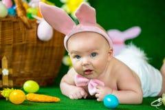 一个逗人喜爱的滑稽的婴孩的画象在复活节兔子耳朵穿戴了用鸡蛋 图库摄影