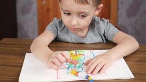 一个逗人喜爱,微笑的孩子在家坐在桌上并且画在纸的一张图片与铅笔或色的白垩 童年 股票录像