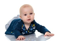 一个逗人喜爱,非常小女孩在一白色backgr的地板上说谎 库存照片