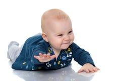 一个逗人喜爱,非常小女孩在一白色backgr的地板上说谎 免版税库存图片