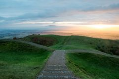 一个道路标题到下坡里 在英国阵营铁器时代小山堡垒,莫尔文小山 当太阳升起在有薄雾的平均观测距离 库存图片