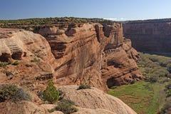 一个遥远的峡谷的红色岩石墙壁 库存照片