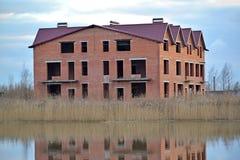 一个部分公寓村庄的建筑在河岸的 免版税库存图片