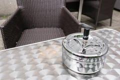 一个酒吧大阳台一个雨天,在金属桌上的烟灰缸 咖啡馆桌和椅子,奥地利 库存照片