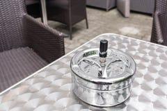 一个酒吧大阳台一个雨天,在金属桌上的烟灰缸 咖啡馆桌和椅子,奥地利 免版税库存照片