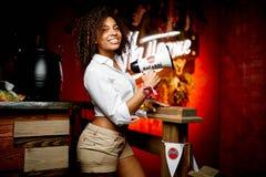 一个酒吧的美丽的女服务员在白色衬衣 免版税库存图片