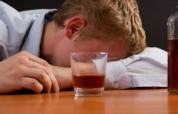 一个醉酒的人是睡着在桌上 图库摄影