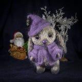 一个野兔的玩偶在紫色的编织了等待圣诞老人的衣裳 库存照片