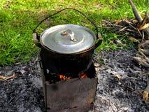 一个野营的平底锅的特写镜头烹调的风行诱饵有美好的风景背景的鱼汤 免版税库存照片