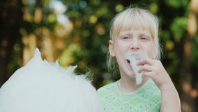 一个金发女孩的画象,吃甜棉绒在公园 一个清楚的夏日,一个愉快的假期 股票视频