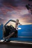 一个金发碧眼的女人的减速火箭的画象一辆蓝色汽车的 库存照片