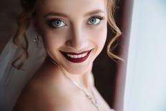 一个金发碧眼的女人的特写镜头有卷毛微笑的雪白牙和黑暗的嘴唇的 有大灰色美丽的眼睛的一个女孩 早晨  免版税图库摄影