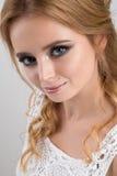 一个金发碧眼的女人的特写镜头在一根白色鞋带的画象有蓝眼睛的和卷毛冠上 库存照片
