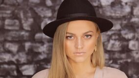 一个金发碧眼的女人的画象黑帽会议的反对砖墙背景 股票视频