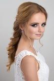 一个金发碧眼的女人的画象有晚上构成的和会集在白色鞋带上面的一根辫子头发 库存图片