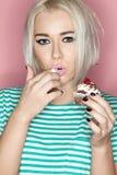 一个金发碧眼的女人的画象有蛋糕的 免版税图库摄影