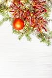 一个金子Xmas球和树枝在白纸 免版税库存照片