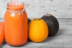 一个金属螺盖玻璃瓶用健康红萝卜汁,黄色和绿色夏南瓜,在轻的木被弄脏的背景的被剥皮的红萝卜 免版税库存照片