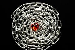 一个金属链子的圈子在黑背景的在透明塑料的构成心脏的中心 免版税库存照片