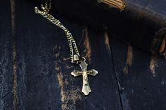 一个金黄十字架谎言和古老圣经在桌上 库存图片