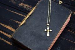 一个金黄十字架谎言和古老圣经在桌上 库存照片