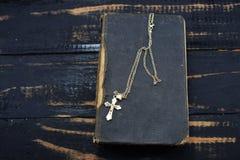 一个金黄十字架谎言和古老圣经在桌上 免版税库存照片