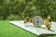 一个金黄指南针和一张地图喷泉和绿色的 库存照片
